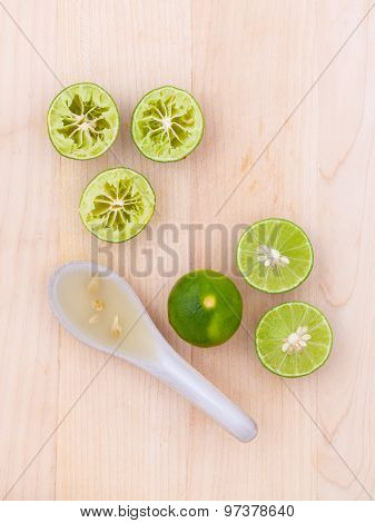Fresh Lime Juice In Spoon And Lime Slice On Wooden Background.