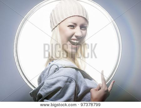 Young And Sexy Happy Blond Woman Posing In Studio Environment In Hoody And Warm Hat.