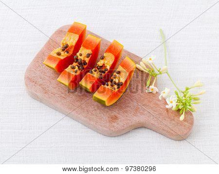 Fresh Papaya And Papaya Slice With Papaya Leaf On Cutting Board.