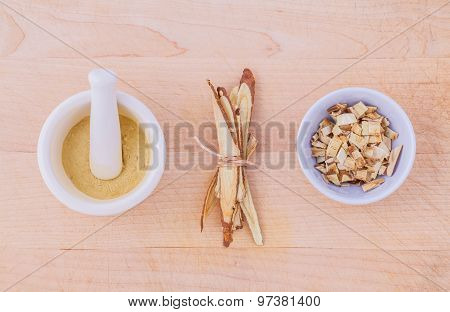 Licorice Herbal Medicine Including Powder, Chopped And Sliced Root And Mortar On Wooden Table