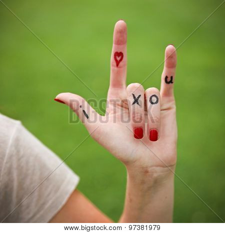 a young girl's hand with lettering i heart x o u written on during summer making the rock on sign