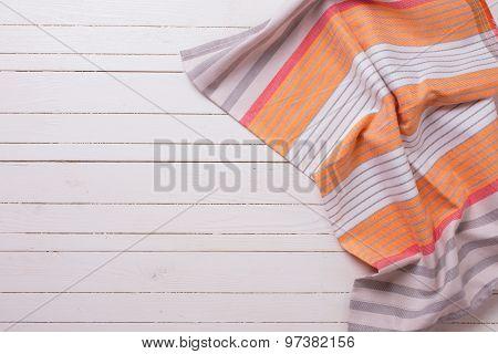 Orange  Kitchen Towel  On White Wooden Background.