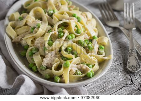 Homemade Pasta With Green Peas, Chicken And Cream Sauce On A Light Wooden Background