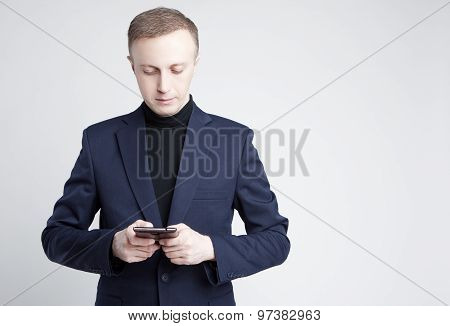 Portrait Of Caucasian Businessman In Stylish Blue Suite Posing With Cell Phone
