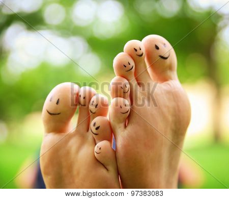 smiley faces on a pair of feet on all ten toes in a park setting