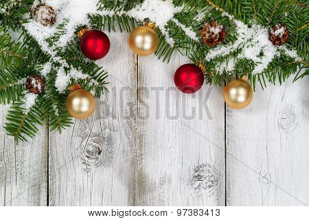Snow Covered Fir Branches And Ornaments On Rustic White Wooden Boards
