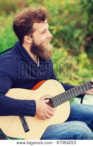 adventure, travel, tourism, music and people concept - smiling man playing guitar in camping