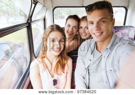friendship, travel, vacation, summer and people concept - group of happy teenage friends with smartphone traveling by bus