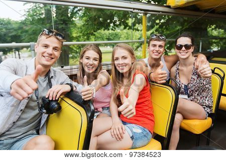 friendship, travel, vacation, summer and people concept - group of happy friends with digital camera traveling by tour bus and showing thumbs up