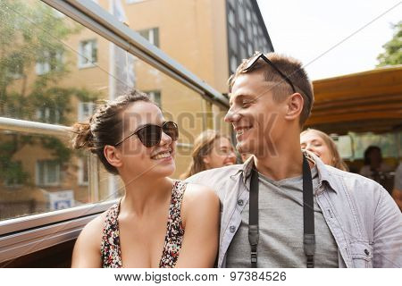 travel, tourism, summer vacation, sightseeing and people concept - smiling teenage couple in sunglasses traveling by tour bus