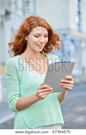 tourism, travel, leisure, people and technology concept - smiling redhead teenage girl or young woman with tablet pc on city street
