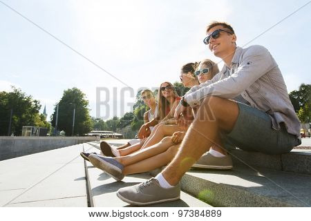 friendship, leisure, summer and people concept - group of smiling friends in sunglasses sitting on city street