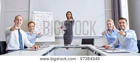 business, people and teamwork concept - group of smiling businesspeople meeting and pointing finger at you in office