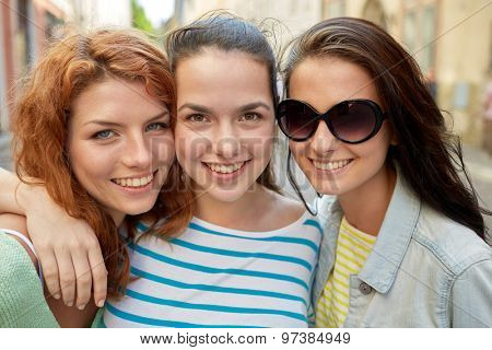 vacation, weekend, leisure and friendship concept - smiling happy young women or teenage girls on city street