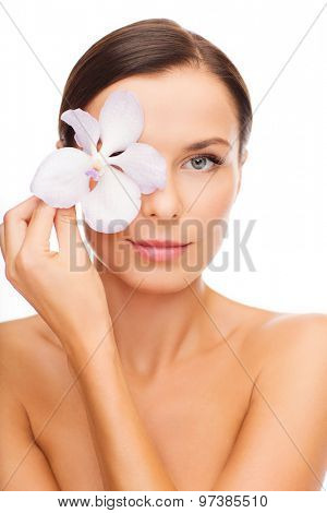 health and beauty concept - relaxed woman with orchid flower over eye