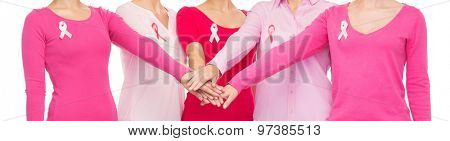 healthcare, people, gesture and medicine concept - close up of women in blank shirts with pink breast cancer awareness ribbons putting hands on top over white background