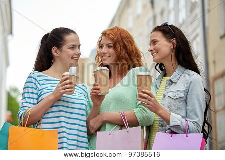 vacation, sale, takeaway drinks, leisure and friendship concept - smiling happy young women or teenage girls with shopping bags drinking coffee from disposable paper cups on city street