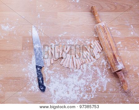Top view on raw homemade pasta with flour, sea salt and vintage rolling pin over old wooden table