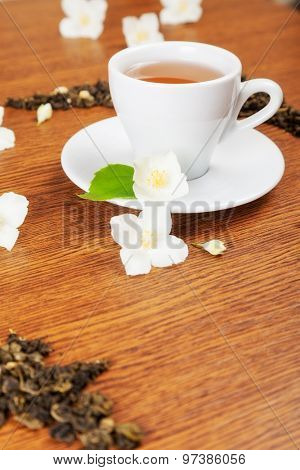 white cup and saucer with jasmine flowers on a wooden table. background