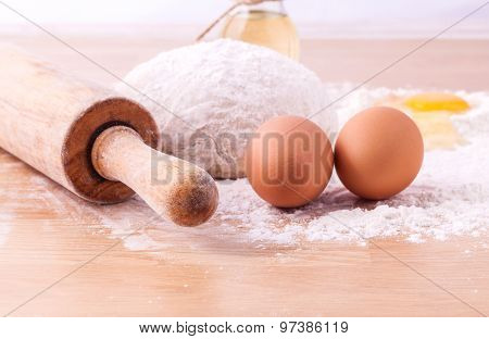 Baking Ingredients Including Fresh Eggs, Flour And A Rolling Pin On Wooden Table.