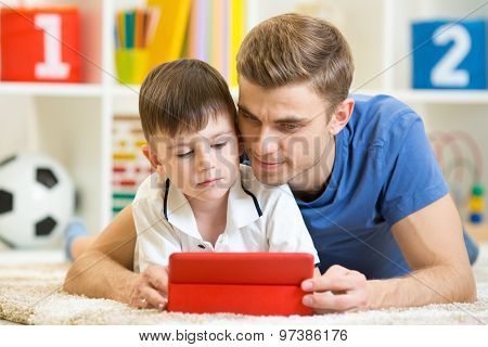 Family - father and son with tablet pc on floor at home. Man and child relaxing at tablet computer.