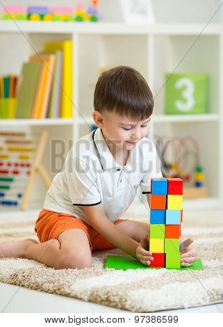 Child little boy playing with cubes, smiling