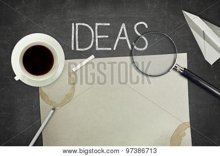 Ideas concept on black blackboard with empty paper sheet