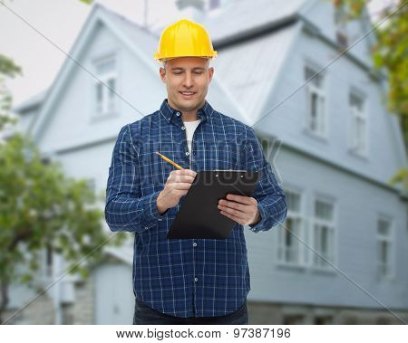 repair, construction, building, people and maintenance concept - smiling male builder or manual worker in helmet with clipboard taking notes over living house background