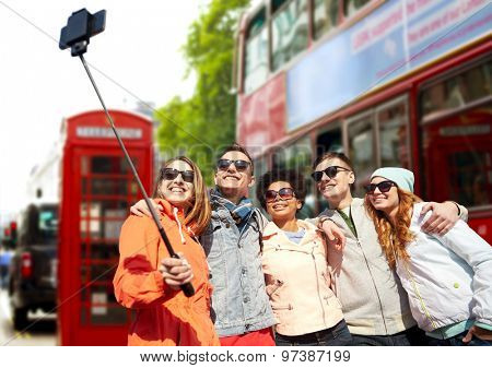 tourism, travel, people, leisure and technology concept - group of smiling teenage friends taking selfie with smartphone and monopod over london city street background