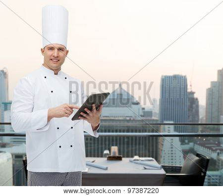 cooking, profession and people concept - happy male chef cook holding tablet pc computer over city restaurant lounge background