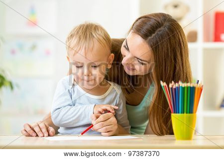 cute child drawing with mother help