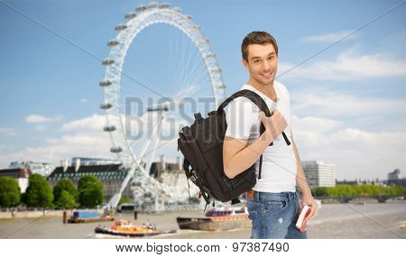 people, travel, tourism and education concept - happy young man with backpack and book over london ferry wheel background