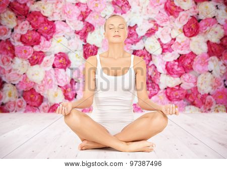 people, health, wellness and meditation concept - woman in underwear meditating in yoga lotus pose on wooden floor over wall of flowers background