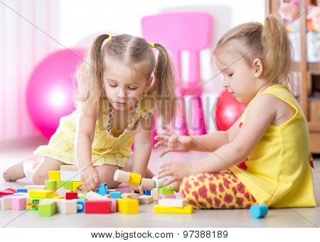 Children playing with wooden blocks sitting on the floor in room