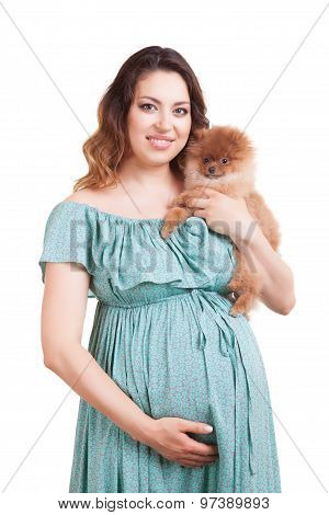 Pregnant Woman With Puppy In Hands Over White Background