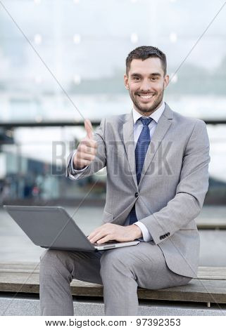 business, education, technology, gesture and people concept - smiling businessman working with laptop computer showing thumbs up on city street
