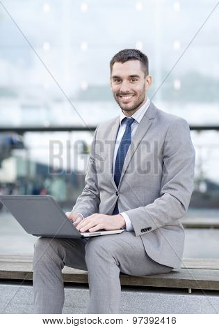 business, education, technology and people concept - smiling businessman working with laptop computer on city street
