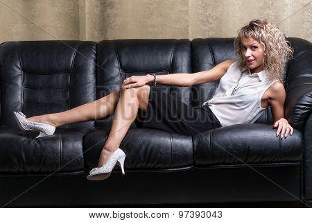 very beautiful, sensual sexy blonde girl lying on a balck sofa