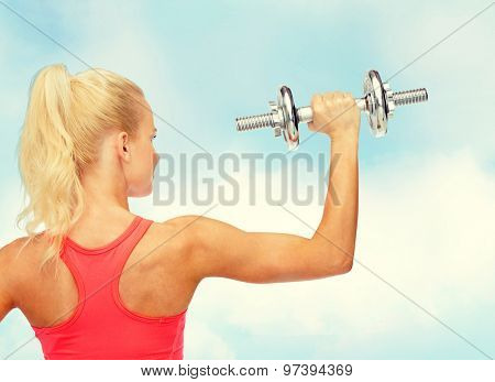 fitness, healthcare and exercise concept - young sporty woman with heavy steel dumbbell from the back