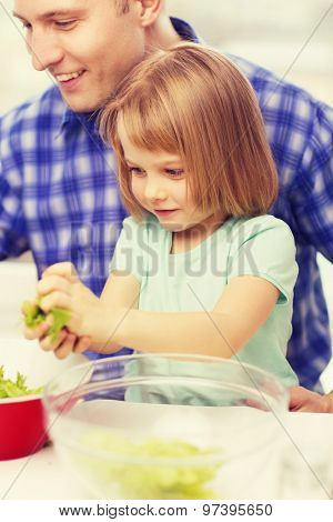 family, child, food and home concept - smiling father and little girl at kitchen cooking salad