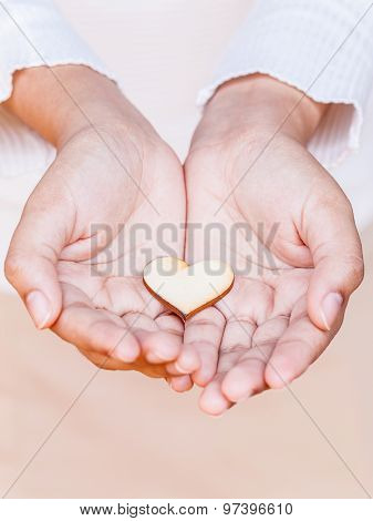 Girl Holding Wood Shape Of Heart . Concept For Giving Love.