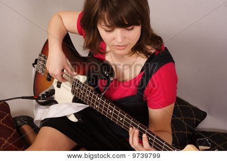 young beautiful woman with a bass guitar