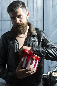 foto of moustache  - Handsome unshaven young man with beard and moustache in brown leather jacket and chain opening round red white striped present box with ribbon bow standing on grey wooden background vertical picture - JPG