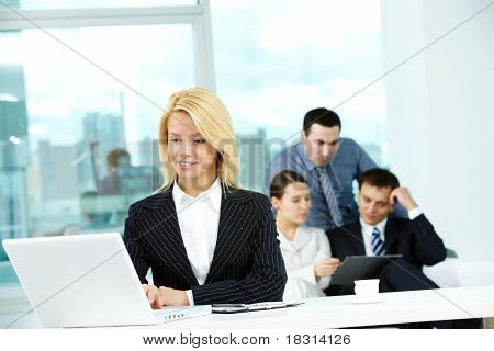 Portrait of pretty secretary looking at laptop screen in working environment