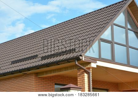poster of Building Modern House Construction with metal roof rain gutter system and roof protection from snow snow bar (Snow guard). Roof Snow Guards: Building Materials & Supplies. Attic skylight window.