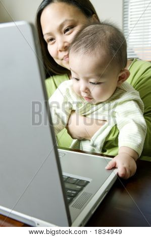 Mother Holding Baby Son While Working On Laptop