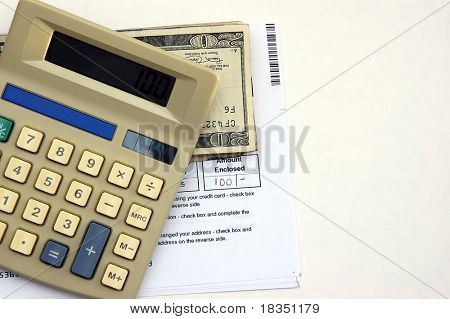 A Calculator, check book and a bill against a white background symbolizing paying bills