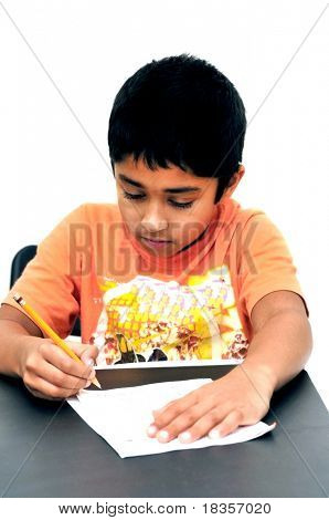 An handsome Indian kid doing his homework diligently