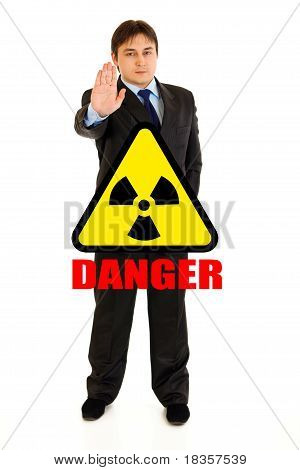 Concept-radiation hazard! Full length portrait of confident businessman showing stop gesture isolate