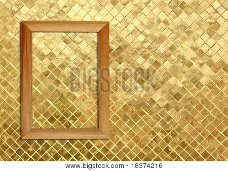 blank wooden frame on gold mosaic wall
